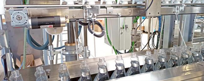 Eine Maschine setzt Sprühaufsätze auf Reinigungsflaschen